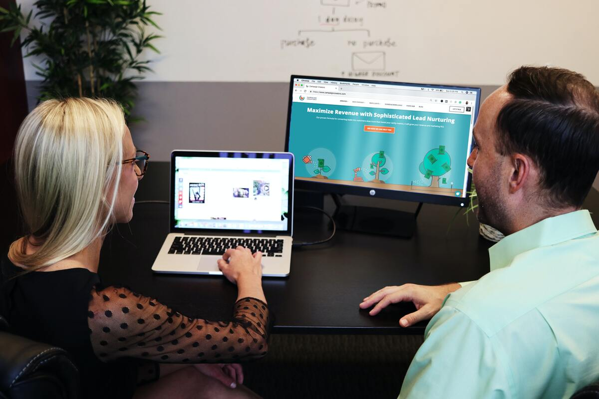 woman and man talking in front a laptop discussing lead generation
