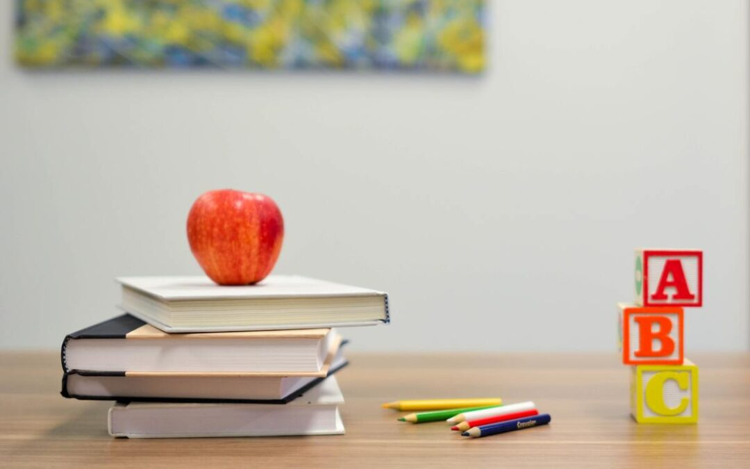 There are Red apples on books, colored pencils and boxes with A B C on them are on a table