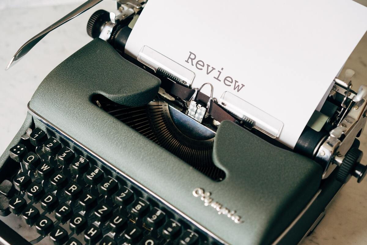 A white page with review text on it is in a black typewriter