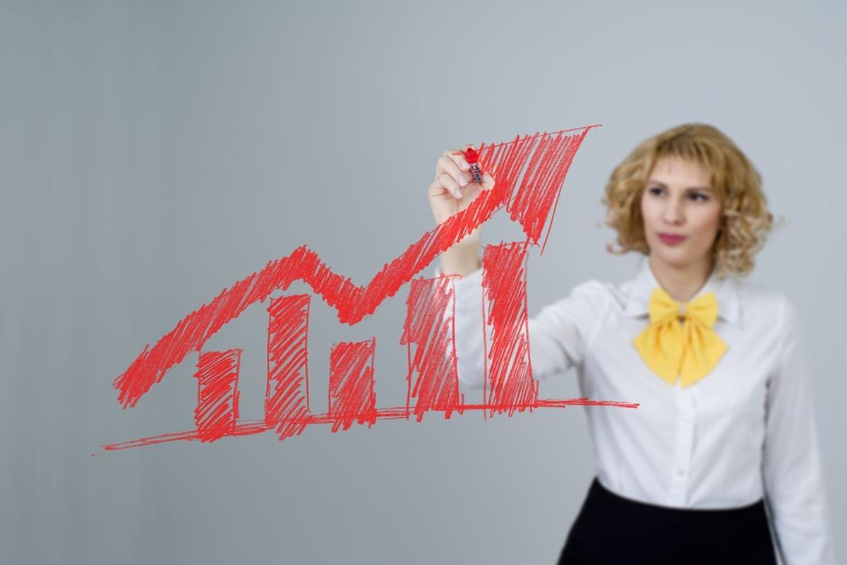 A girl pointing at sales increase graph